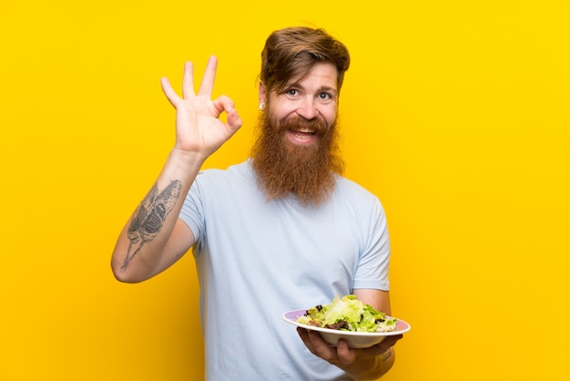 Redhead man with long beard and with salad over isolated yellow wall showing ok sign with fingers Premium Photo