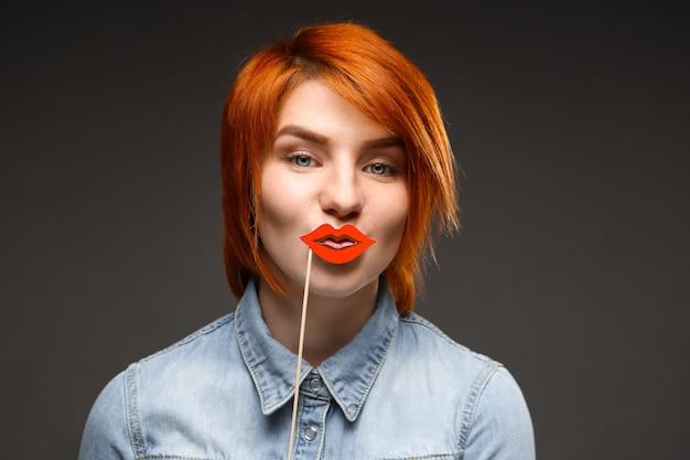 Рыжая глупая женщина держит поддельные губы и улыбается Бесплатные Фотографии