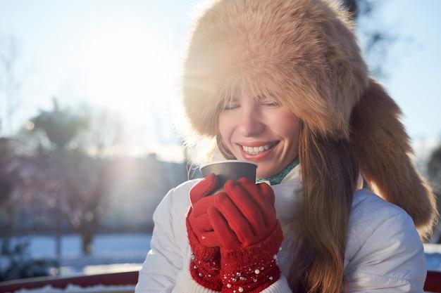 キツネの毛皮の帽子と白いジャケットを着た赤毛のスキニーガール。冬の寒い日にコーヒーを飲みながら笑っています。 Premium写真