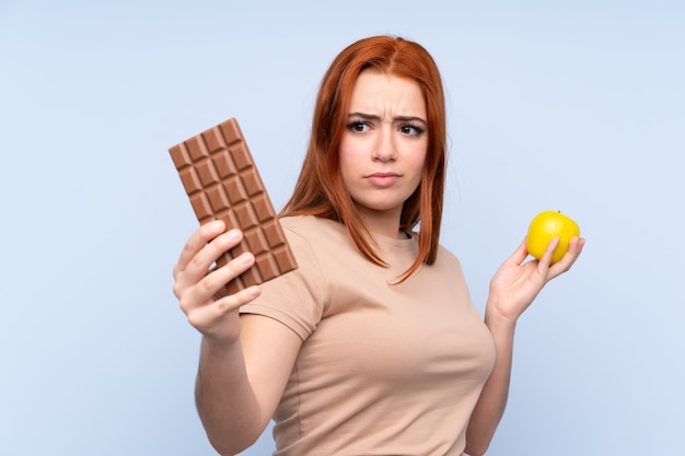 Redhead teenager girl over blue having doubts while taking a chocolate tablet in one hand and an apple in the other Premium Photo