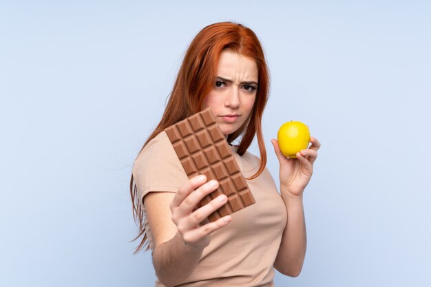 Redhead teenager girl over blue taking a chocolate tablet in one hand and an apple in the other Premium Photo