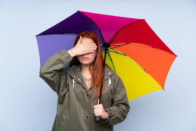 Redhead teenager girl holding an umbrella over blue covering eyes by hands Premium Photo