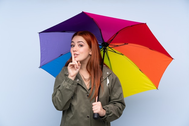 Redhead teenager girl holding an umbrella over blue doing silence gesture Premium Photo