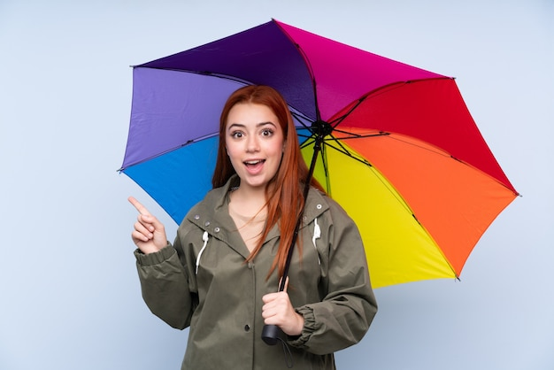 Redhead teenager girl holding an umbrella over blue pointing finger to the side Premium Photo