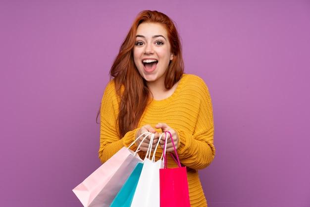 Рыжая девушка-подросток над изолированной фиолетовой стеной держит сумки и удивляется Premium Фотографии