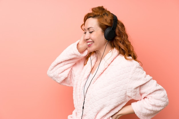 Redhead woman in dressing gown listening music Premium Photo