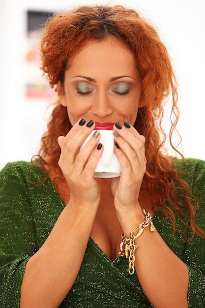 コーヒーを飲む赤毛の女性 無料写真