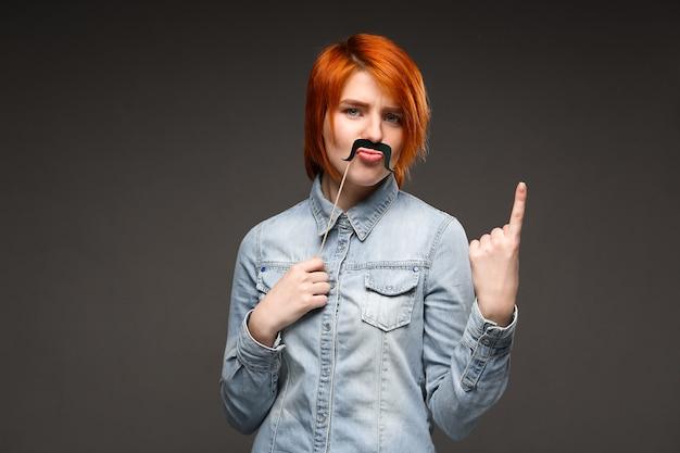 偽の口ひげをゆがめる赤毛の女性 無料写真