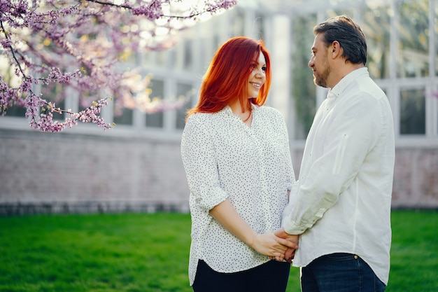 redhead woman in a white blouse standing in a sunny summer park with her boyfriend Free Photo