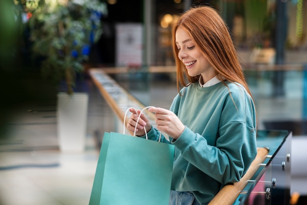 Redhead woman looking inside shopping bag Free Photo