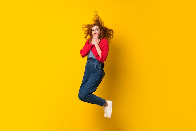 Redhead woman with overalls jumping over isolated yellow wall Premium Photo