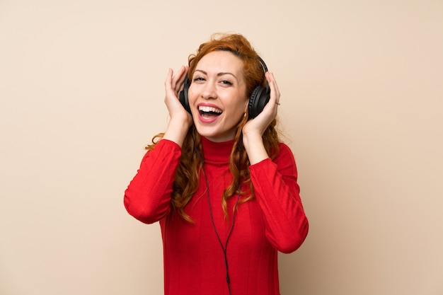 Redhead woman with turtleneck sweater listening to music with headphones Premium Photo