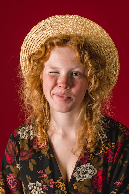 Redhead young female winking and looking at camera Free Photo