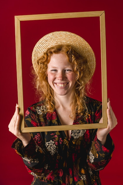 Redhead young woman smiling and holding wooden frame Free Photo