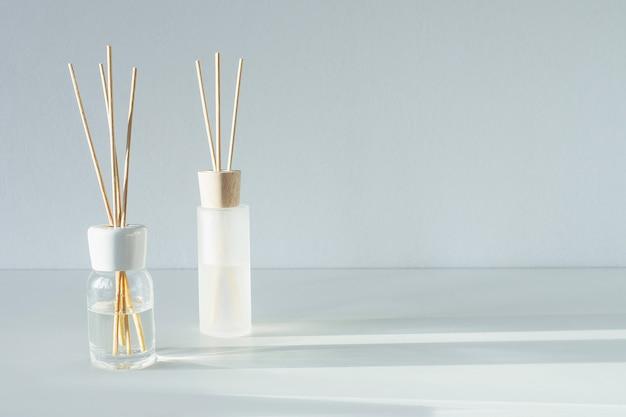テーブルのリードディフューザー。花の香りのあるアロマスティック。商業フラットレイアウト、正面図。アロマセラピーの香り。コピースペース Premium写真