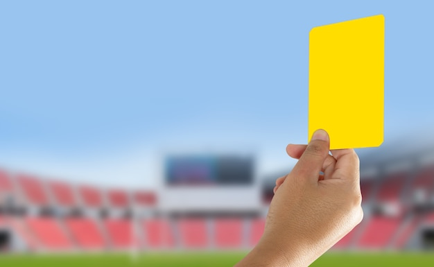 Referee showing yellow card in the field Premium Photo
