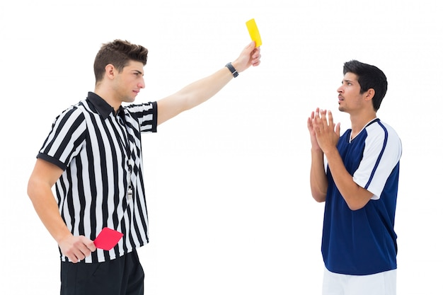 Referee showing yellow card to football player Premium Photo