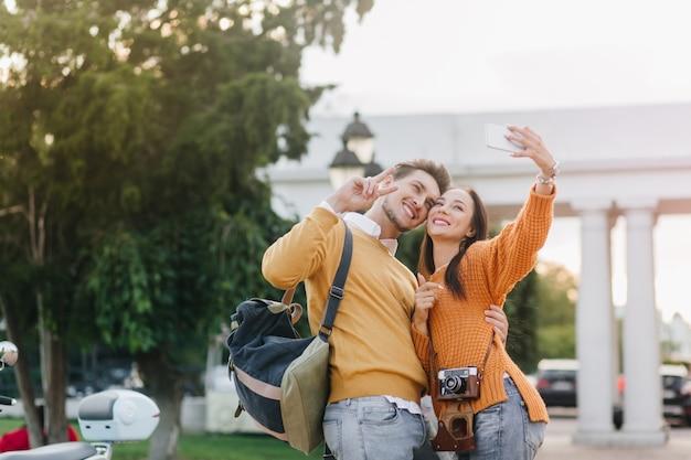 배경에 흰색 구조와 주황색 셔츠에 잘 생긴 남자와 셀카를 만드는 세련된 검은 머리 여자 무료 사진