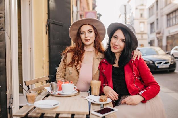카페에서 그녀의 여자 친구를 껴안은 세련된 빨간 머리 여자 무료 사진