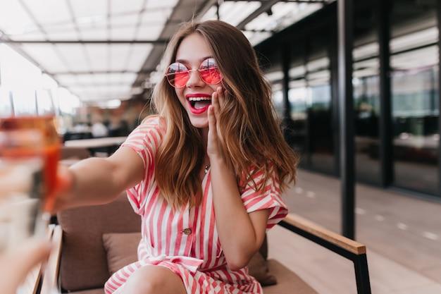 Утонченная молодая дама в солнечных очках празднует что-то в кафе. крытый снимок улыбающейся великолепной девушки в летнем полосатом платье. Бесплатные Фотографии