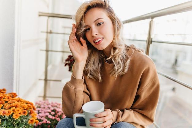 Raffinata giovane donna che beve il tè al balcone. ragazza abbastanza bionda che gode del caffè al mattino. Foto Gratuite