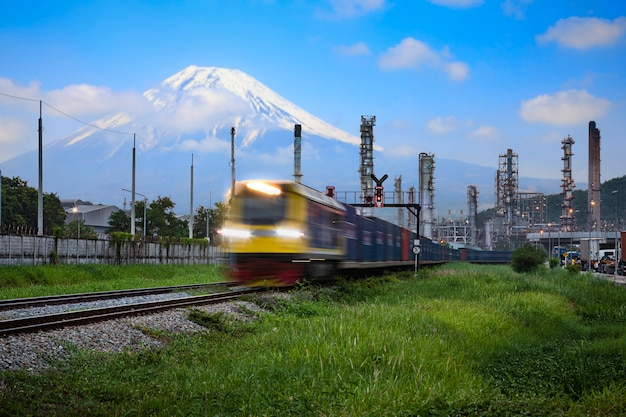 Refinery oil and petroleum industry factory zone and containers cargo logistics train transportation open lighting movement foreground with fuji mountain and blue sky Premium Photo