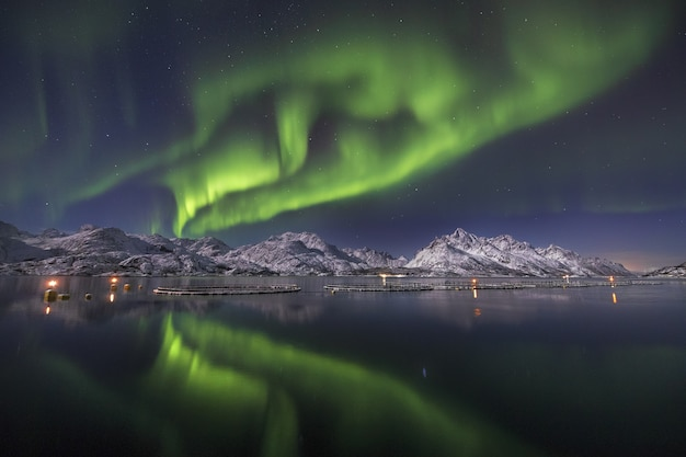 Reflection of the beautiful northern lights in he water surrounded by snow covered mountains Free Photo