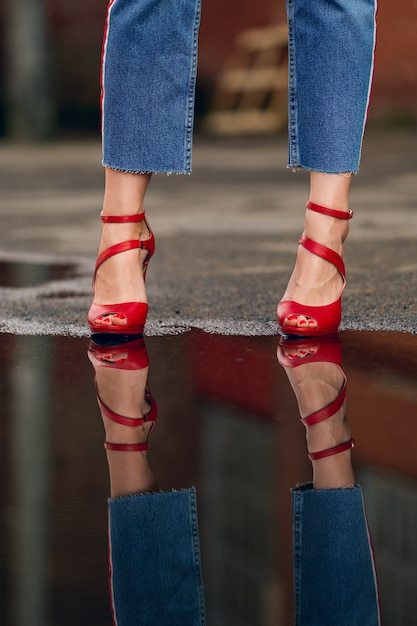 Reflection of female legs in jeans and red  shoes in puddle on asphalt Premium Photo