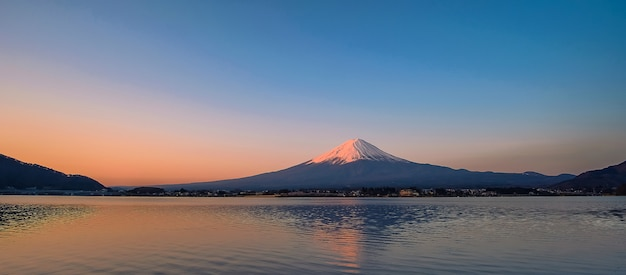 Reflection of fuji mountain with snow capped in the morning sunrise Premium Photo