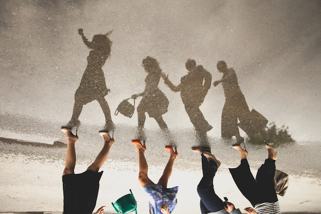 Reflection of a group of people in a puddle on the road. Premium Photo