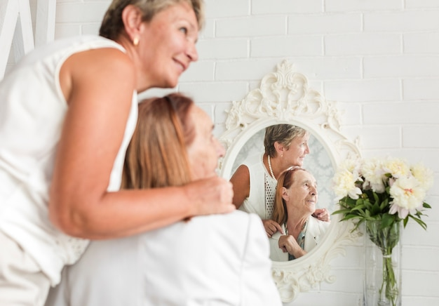 Reflection of mother and daughter on mirror looking away Free Photo
