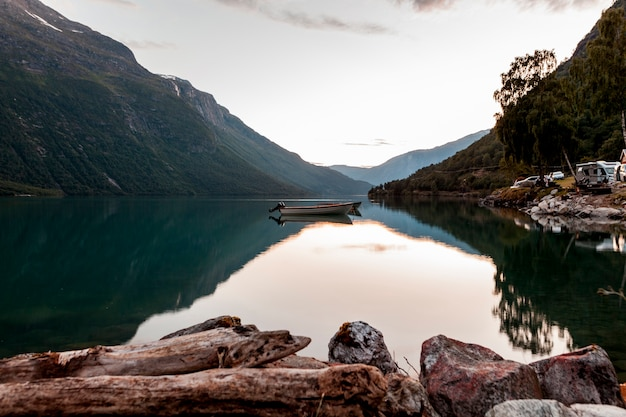Reflection of mountain and boat on calm lake Free Photo