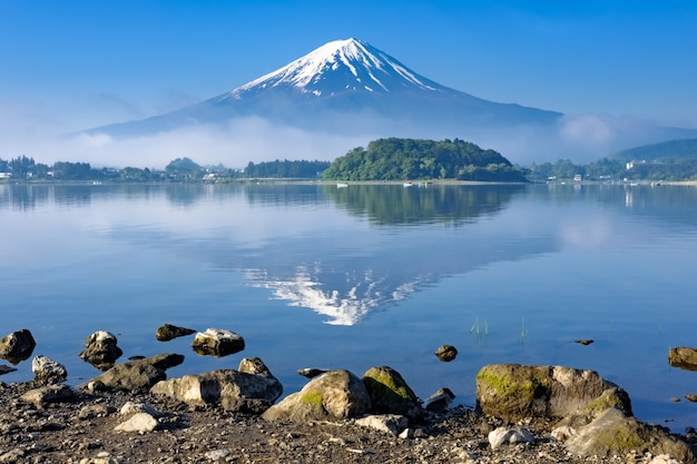 Reflection of mt. fuji with rock shore foreground, kawaguchiko lake, yamanashi Premium Photo