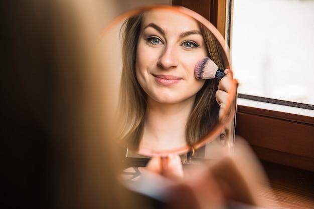 彼女の顔にメイクをしている美しい女性の反射 Premium写真