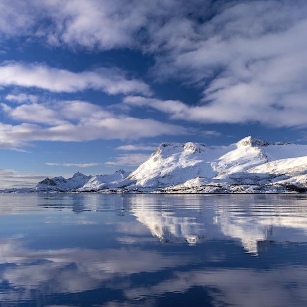 Отражение заснеженной скалы в воде под красивыми облаками на небе в норвегии Бесплатные Фотографии