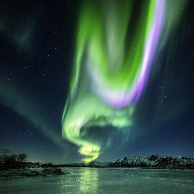ノルウェーで捕獲された夜の湖の美しいオーロラの反射 無料写真
