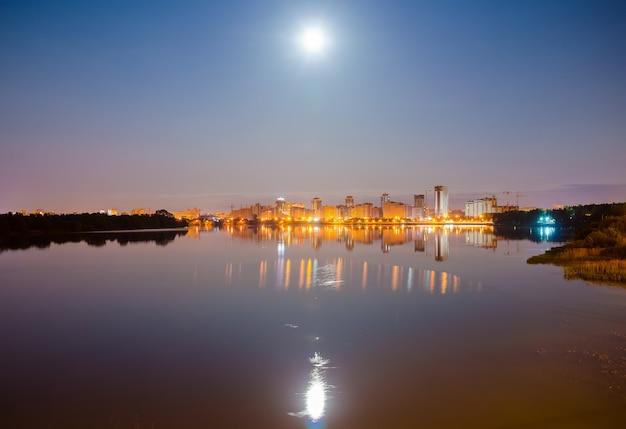 Отражение ночного города на поверхности воды. Premium Фотографии