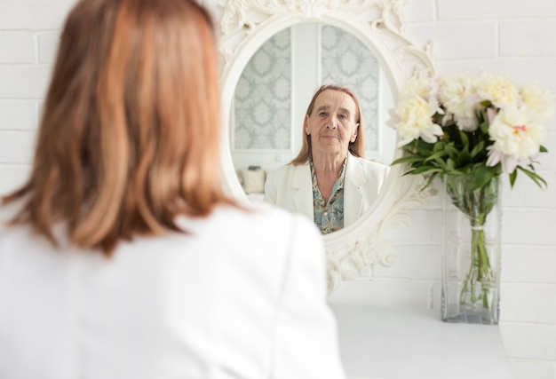 Reflection of senior woman on mirror near beautiful flower vase at home Free Photo
