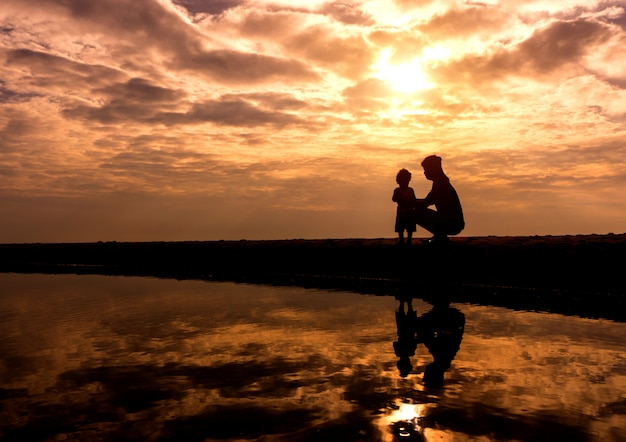 Reflection silhouettemother with her toddler against the sunset Premium Photo