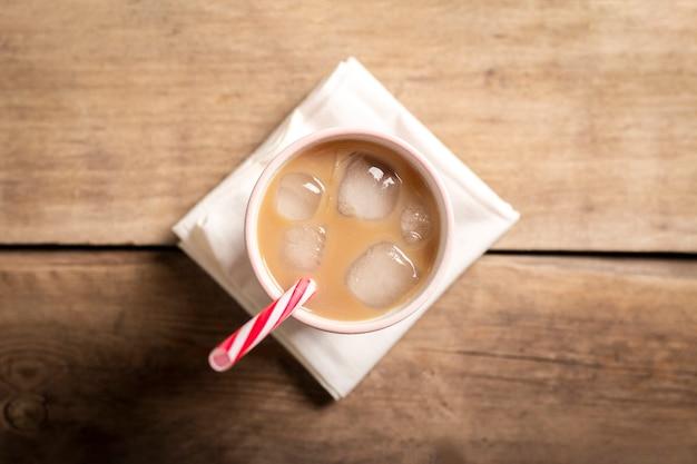 Освежающий и бодрящий кофе со льдом в стакане на деревянном фоне. концепция кафе, утоление жажды, лето. плоская планировка, вид сверху Premium Фотографии