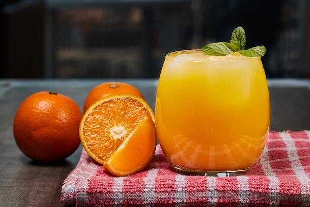 暗い背景の木製テーブルに新鮮なオレンジジュース、氷、オレンジとさわやかなガラス Premium写真
