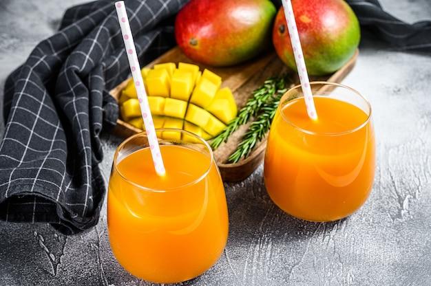 Освежающий сок манго в стакане. серый фон вид сверху Premium Фотографии