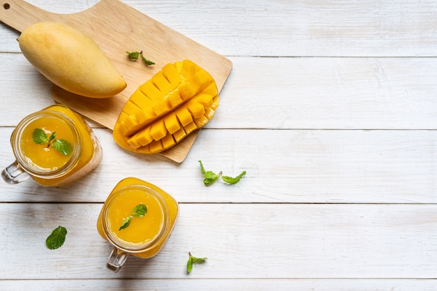 Refreshing mango smoothies in glass with ripe mango on white wooden table and copyspace, top view Premium Photo