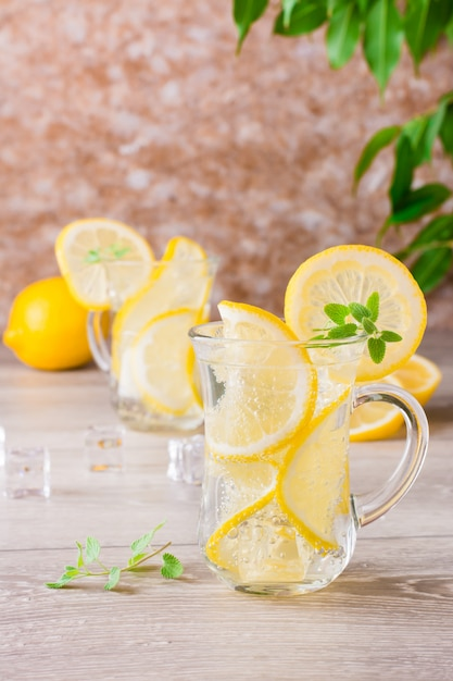 Refreshing mineral water with lemon, mint and ice cubes in glasses on a wooden table Premium Photo