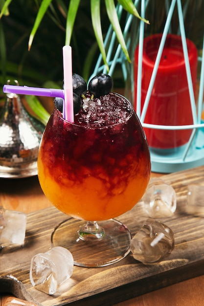 Refreshing red grape beverage in glass with ice cubes Free Photo
