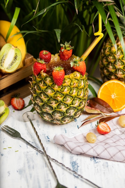 Refreshing summer alcoholic cocktail margarita with crushed ice and citrus fruits inside pineapple with strawberries on kitchen table Free Photo