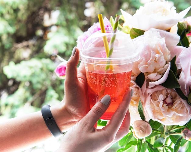 窓の前で女性の手にイチゴと牡丹の花束とさわやかな夏の飲み物 Premium写真