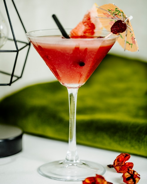 Refreshing watermelon cocktail in a glass with a piece of fruit and decorative umbrella. Free Photo