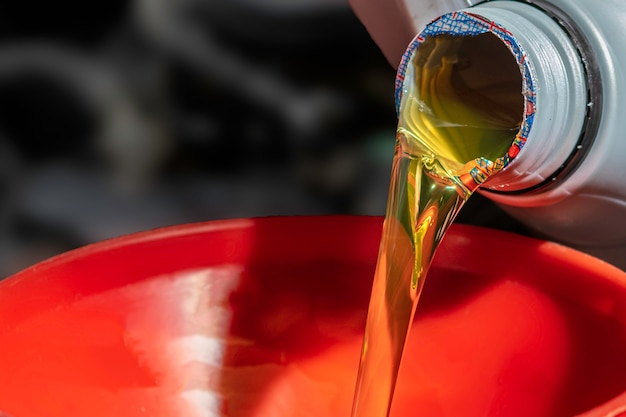 Refueling and pouring oil fill the oil in the engine, maintenance, and performance. Premium Photo