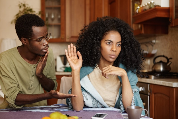 Regretful guilty young afro-american man in glasses offering hand to his angry girlfriend as a sign of reconciliation after serious quarrel but woman seems refusing all apologies and excuses Free Photo